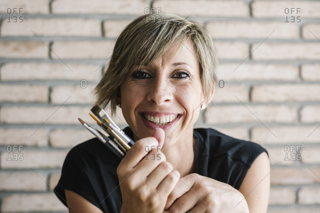 Woman smiling while holding paintbrush against brick wall at home
