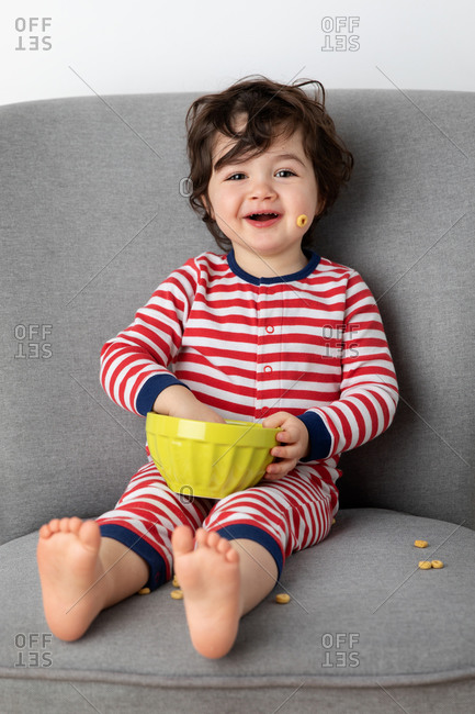 Smiling young child sitting on chair eating cereal