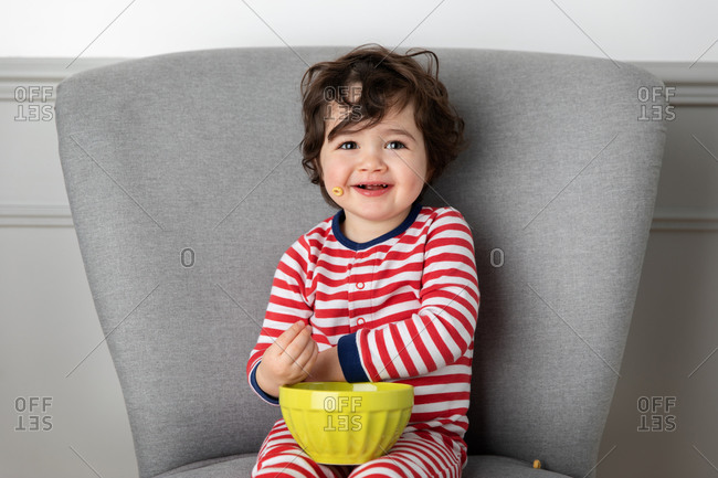 Smiling young boy sitting on chair with bowl of cereal