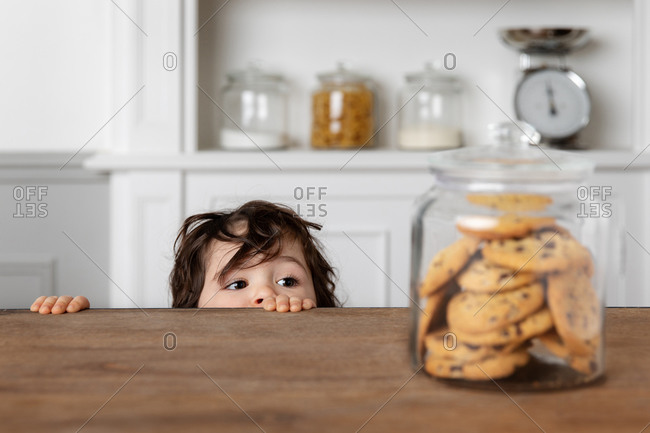 Toddler looking at cookie jar on kitchen table