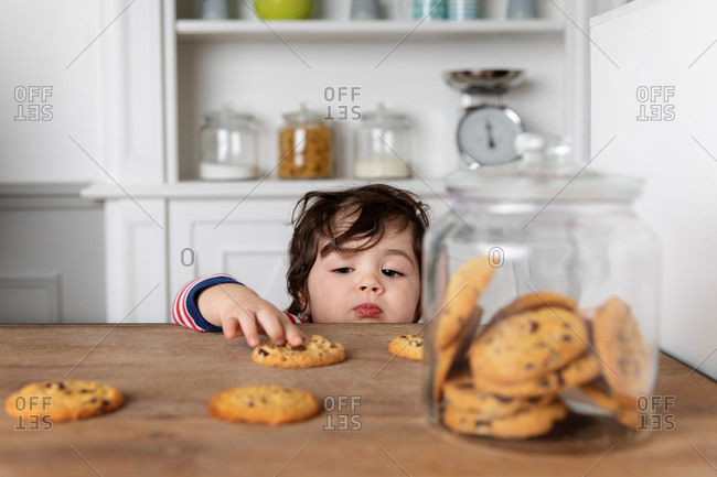 Young child grabbing a cookie on kitchen table
