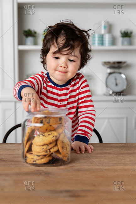 Cute toddler grabbing a cookie from cookie jar