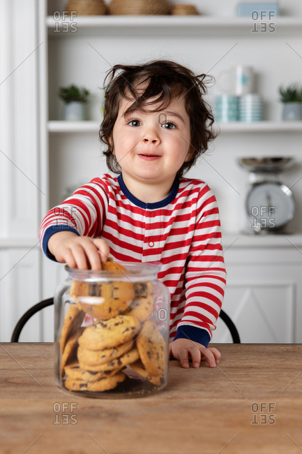 Mischievous toddler getting biscuits from cookie jar on kitchen table