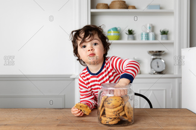 Cute toddler reaching into a cookie jar