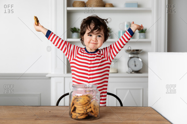 Happy toddler at kitchen table with arms raised holding a cookie