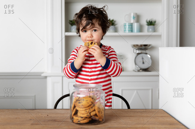 Cute little boy eating a biscuit from cookie jar at kitchen table