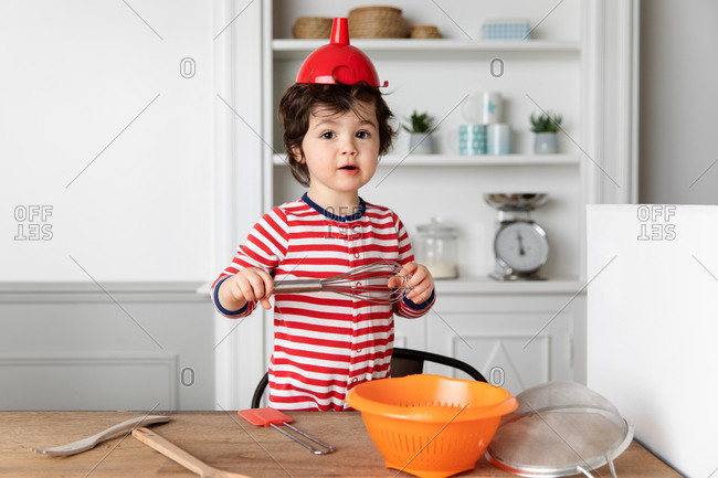 Cute toddler playing with kitchen utensil wearing funnel on head
