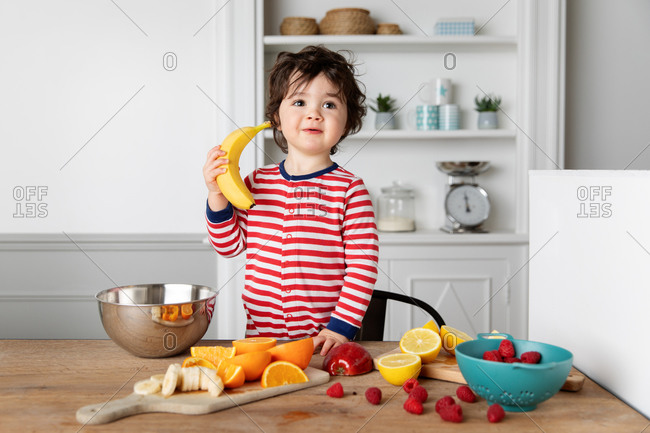 Young boy at kitchen table with fruits playing with a banana
