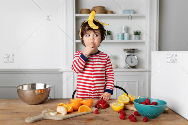 Funny toddler eating fruits in kitchen with banana skin on head