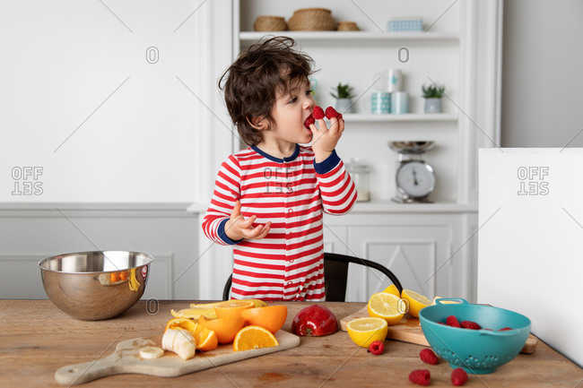 Funny young boy playing with fruits eating raspberries on fingers