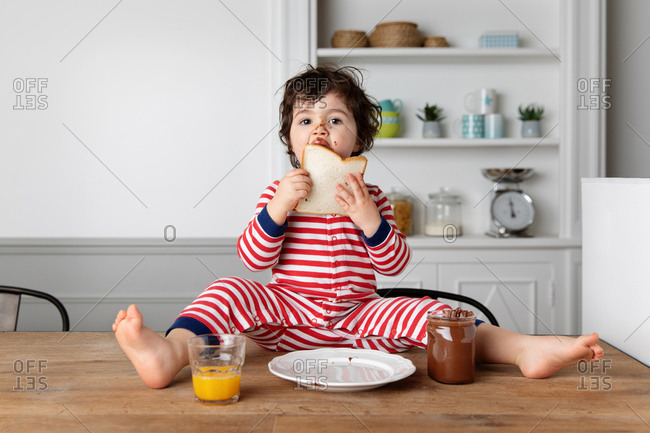 Young boy sitting on kitchen table eating bread with chocolate