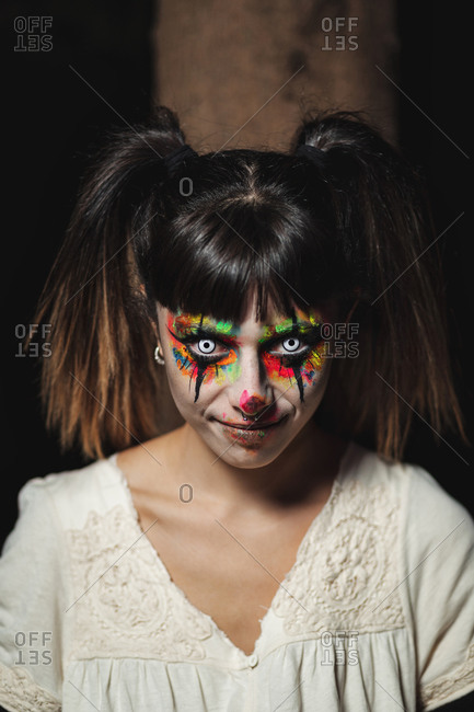Scary young female in colorful contact lenses and with painted face standing in dark forest and smiling creepy while looking at camera on Halloween