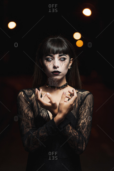 Unemotional female in black dress and with scary makeup standing in white contact lenses on Halloween in darkness while looking at camera