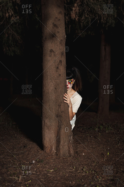 Creepy female with painted face and in contact lenses peeping out of darkens at night on Halloween behind a tree