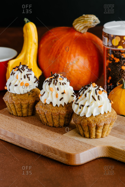 Yummy cupcakes decorated with whipped cream and chocolate on cutting board near colorful vegetables on black background
