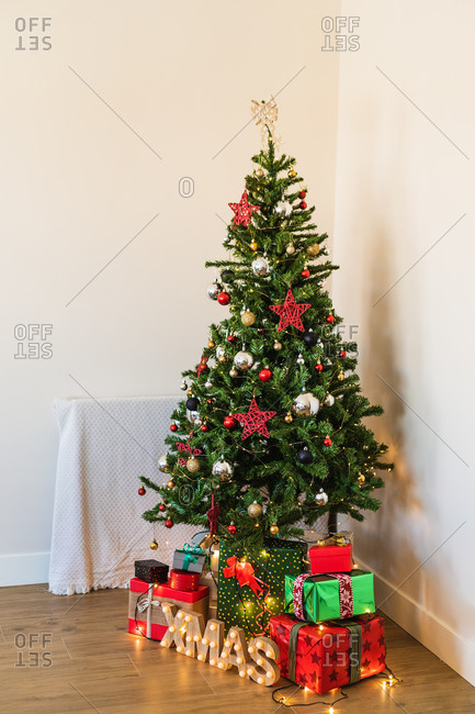 Wrapped present boxes placed under decorated Christmas tree with shiny baubles and garlands in room corner