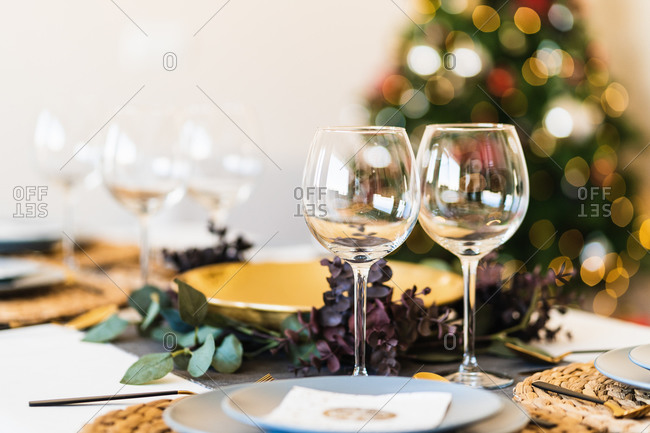 Dining table served with glasses and plates against blurred glowing Christmas tree on Christmas eve at home