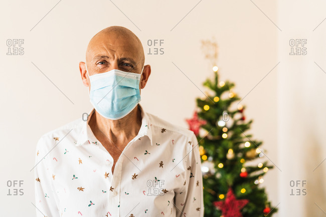 Calm mature male in stylish shirt and protective mask standing against decorated Christmas tree and looking at camera
