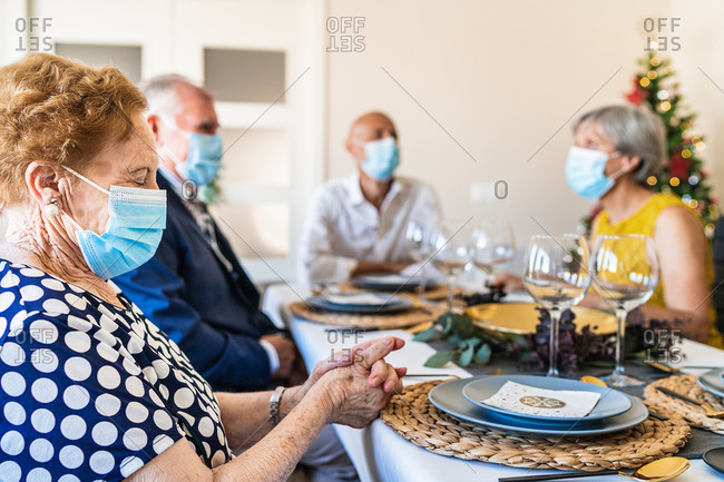 Positive senior friends in smart casual wear and face masks gathering together at dining table and having conversation at Christmas eve