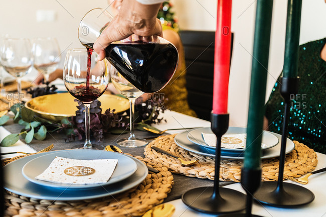 Crop view of hand of anonymous old man serving red wine during Christmas dinner