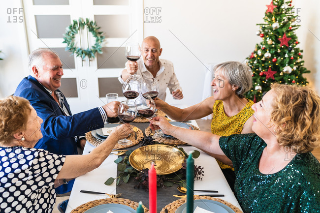 Happy mature friends gathering at festive table near shining Christmas tree and clinking wineglasses while celebrating Christmas eve together