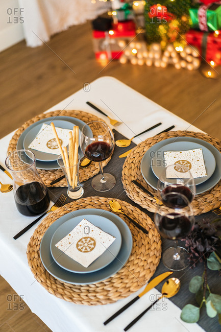From above of ceramic plates near glasses of red wine and cutlery on table during festive event