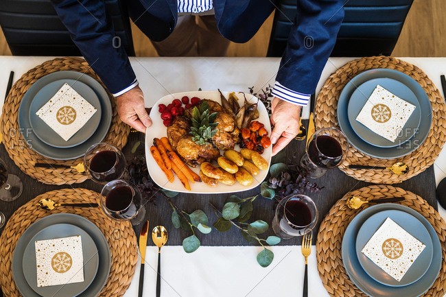 From above of crop unrecognizable male near table with yummy roasted chicken and baked vegetables on plate on Christmas day