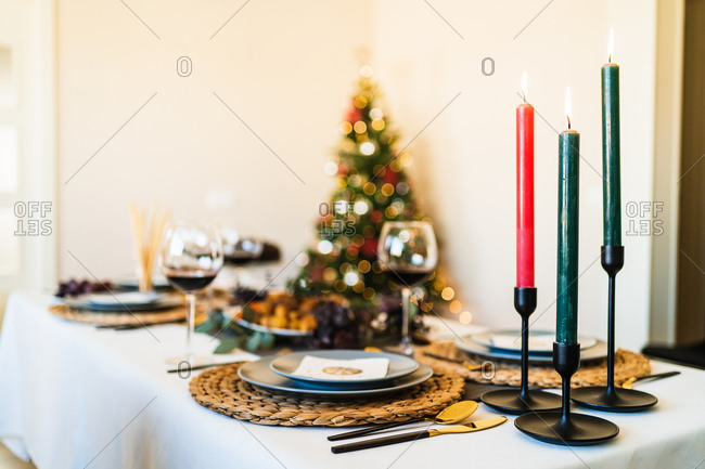 Festive table setting near decorated Christmas tree with glowing garlands before Christmas celebration party