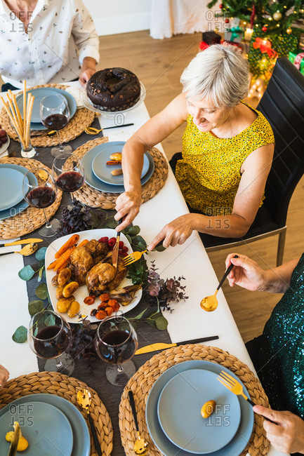 From above of crop unrecognizable people enjoying tasty dish while sitting at table during Christmas holiday