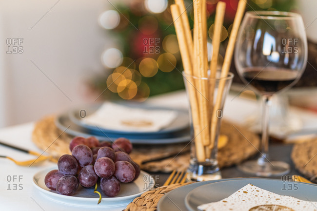 Tasty grapes near glass with crunchy bread sticks and red wine on Christmas day