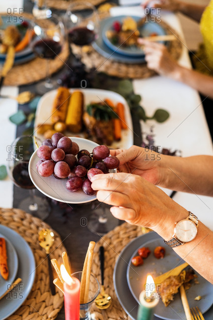 From above of crop anonymous female in wristwatch taking tasty grapes at table during Christmas dinner