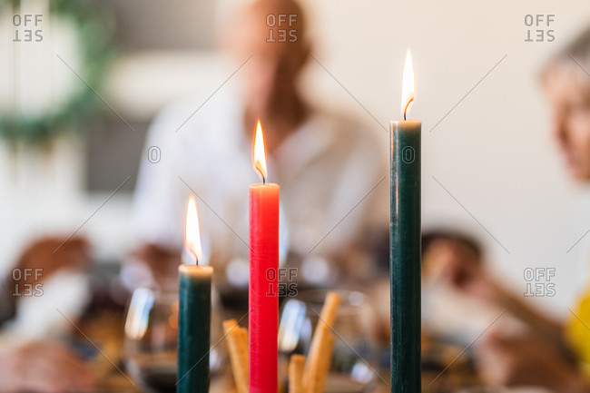 Bright wax candles with shiny flame on table during festive event on blurred background with bokeh effect