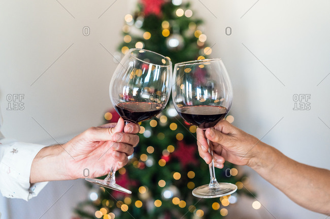 Crop unrecognizable friends with shiny glasses of alcoholic beverage near bright decorative tree during New Year holiday