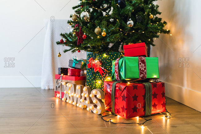 Heap of colorful ornamental present boxes with ribbons near decorative fur tree and shiny letters on floor with garland during festive event