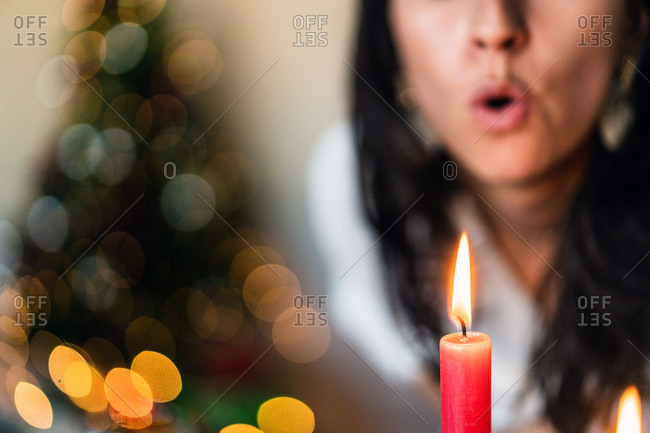 Crop anonymous female blowing on shiny wax candle fire near decorative Christmas tree at home