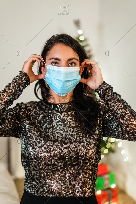 Serious female in festive dress putting on medical mask while standing in room during Christmas celebration and looking at camera