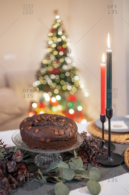 High angle of delicious chocolate cake arranged on table with candles in cozy room on background of Christmas tree with glowing garlands