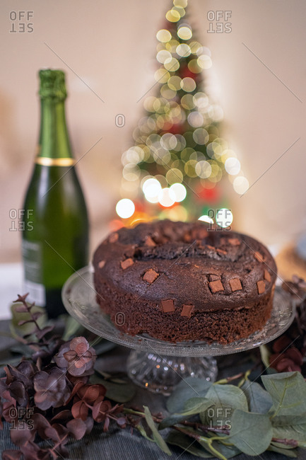 Delicious chocolate cake arranged on table with candles in cozy room on background of Christmas tree with glowing garlands