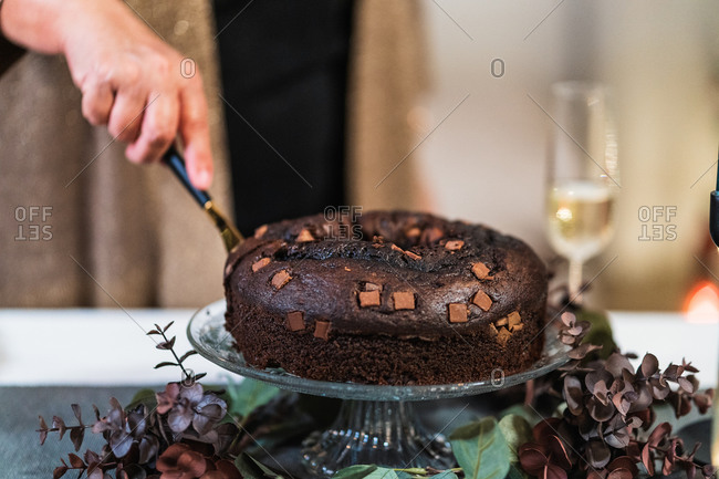 Unrecognizable crop person with knife cutting delicious chocolate cake served on table for Christmas celebration at home
