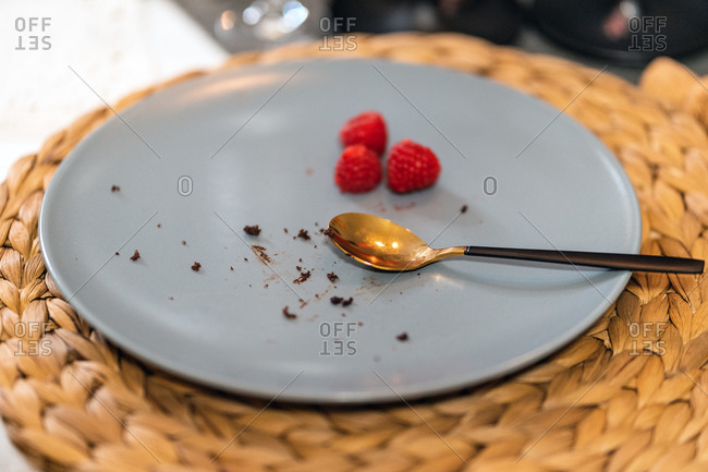 Closeup of dirty plate with spoon and dessert crumbs placed on table after party at home