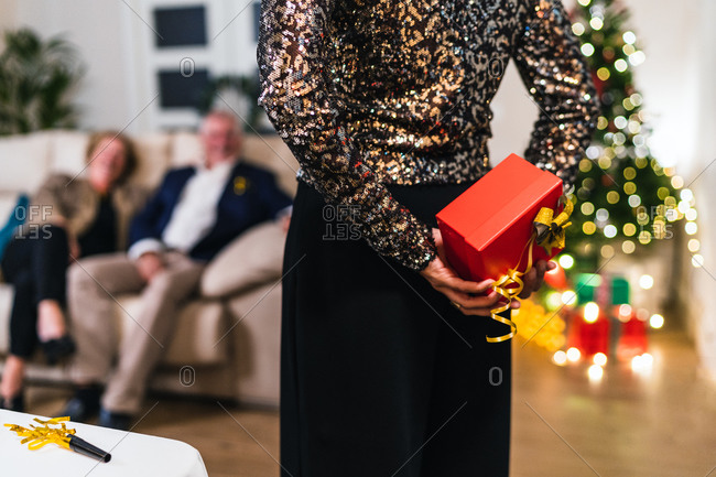 Back view of unrecognizable crop female in festive dress hiding present behind back while celebrating Christmas with friends at home