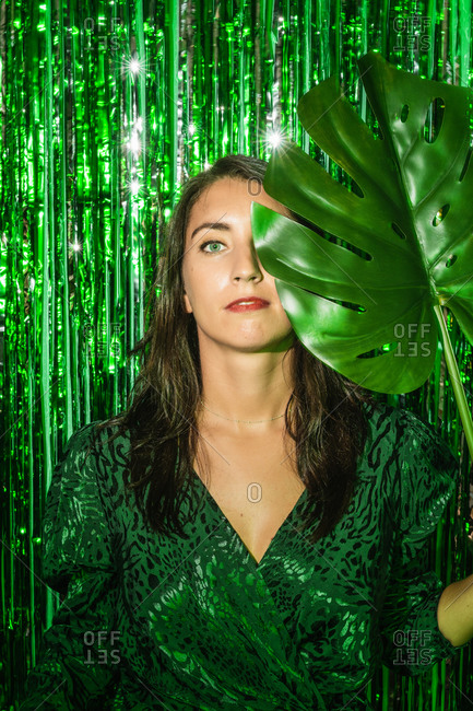 Calm female wearing stylish green dress standing with monstera leaf on background of shining foil tinsel stripes and looking at camera