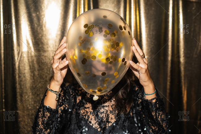 Unrecognizable female wearing festive dress covering face with air balloon with golden confetti while standing on golden background at party