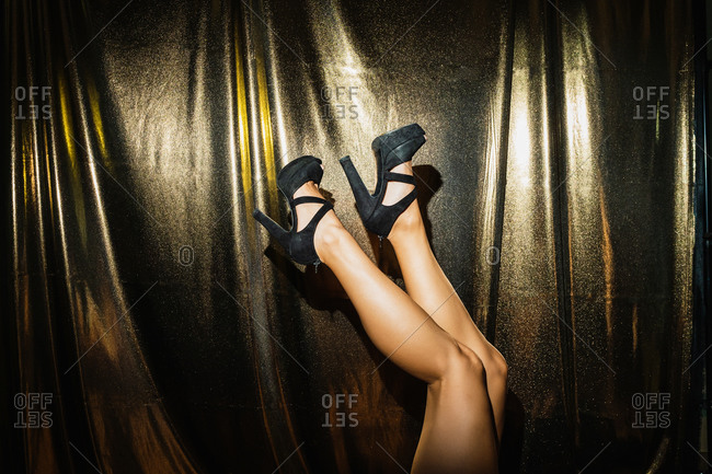 Upside down of crop anonymous female wearing black high heeled shoes on golden background showing glamour party concept
