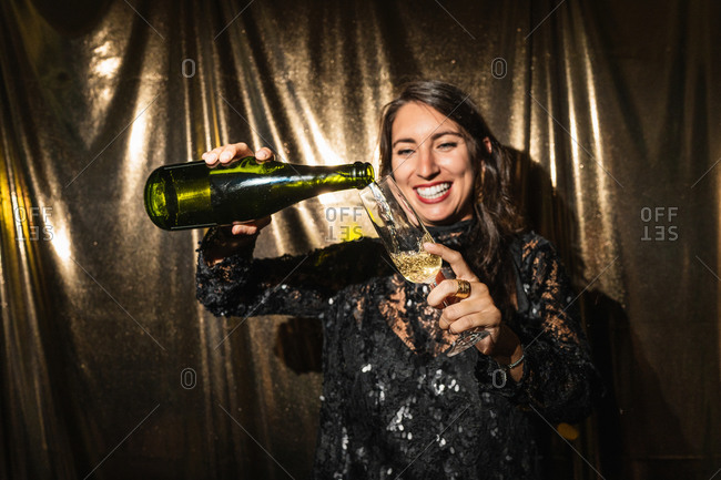 Delighted female in shiny dress standing on golden background and pouring sparkling champagne in glass while enjoying party
