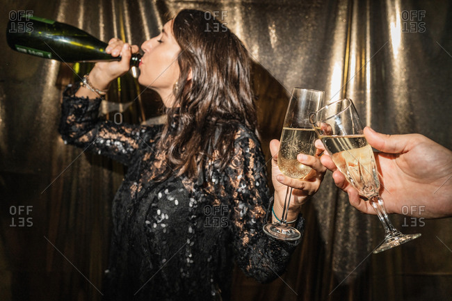 Side view of female in black fancy dress clinking glasses with crop anonymous friend and drinking champagne from bottle while celebrating holiday