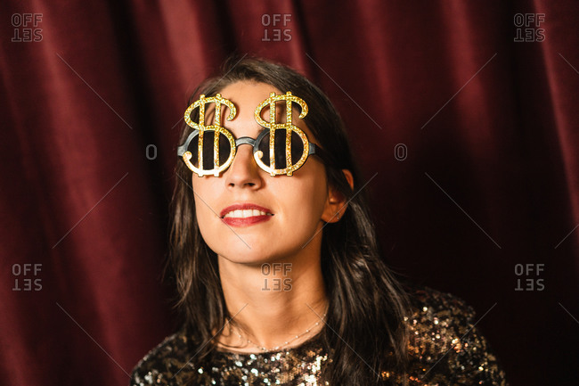 Content female wearing black glamour dress and fancy sunglasses having fun at party while standing on golden background