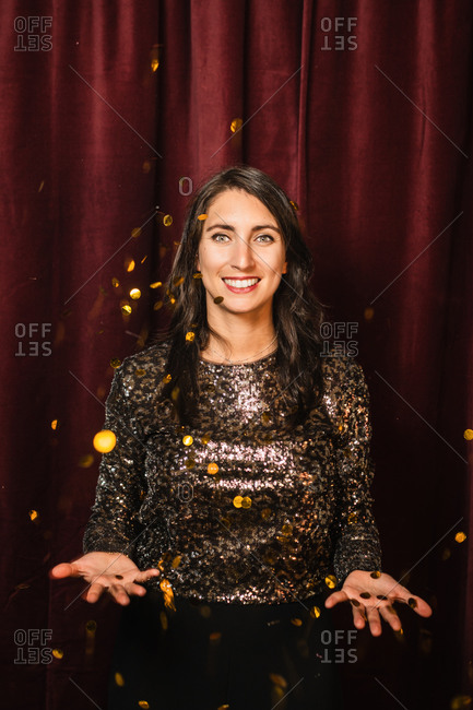 Charming female smiling and merrily tossing golden confetti while standing on red background and enjoying party celebration