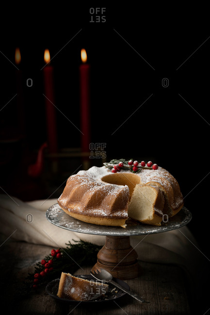 Tasty bundt cake sprinkled with sugar powder and decorated with cranberries served on round tray on table for Christmas party