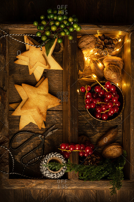 Top view of tasty cookies in shape of star and red berries arranged with illuminated garland and nuts on wooden table in dark room for Christmas celebration